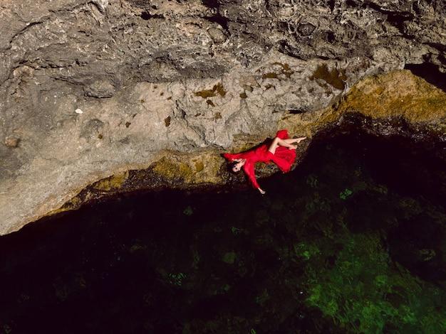 La donna nuota nel mare in un abito lungo rosso con occhiali da sole in estate