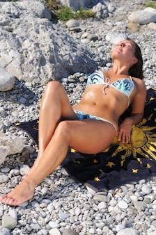 Donna in costume da bagno seduta sulle pietre