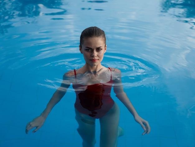 Una donna in costume da bagno sta nell'acqua limpida della piscina e alza le mani ai lati