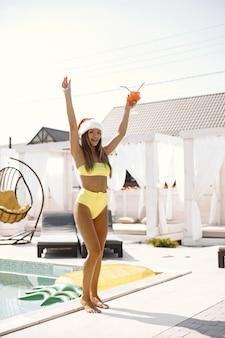Donna in costume da bagno e cappello di natale che tiene in mano un bicchiere e beve cocktail vicino alla piscina.