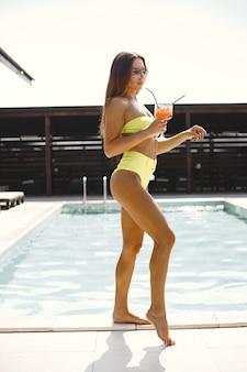 Donna in costume da bagno tenendo il bicchiere e bevendo cocktail vicino alla piscina.