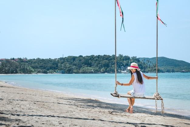 Donna sull'altalena in spiaggia