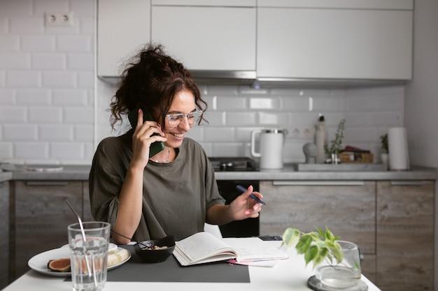Donna in maglietta che fa lavori di carta in cucina mentre fa colazione e parla al telefono
