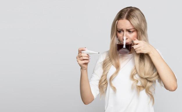 Donna in maglietta che tiene tazza di tè caldo