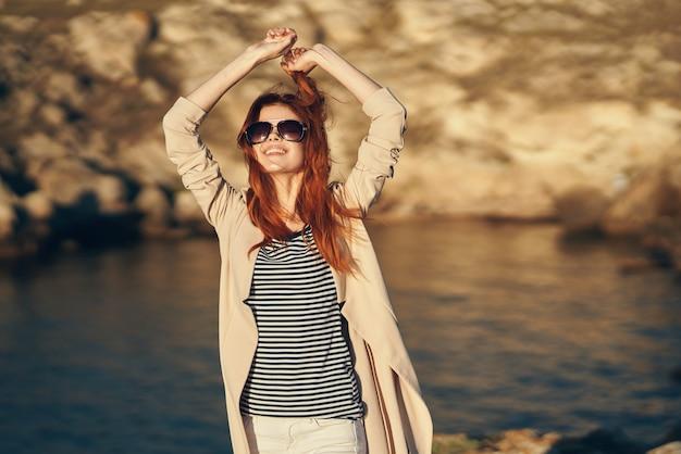 La donna in una maglietta tiene le mani sopra la testa vicino al mare in montagna