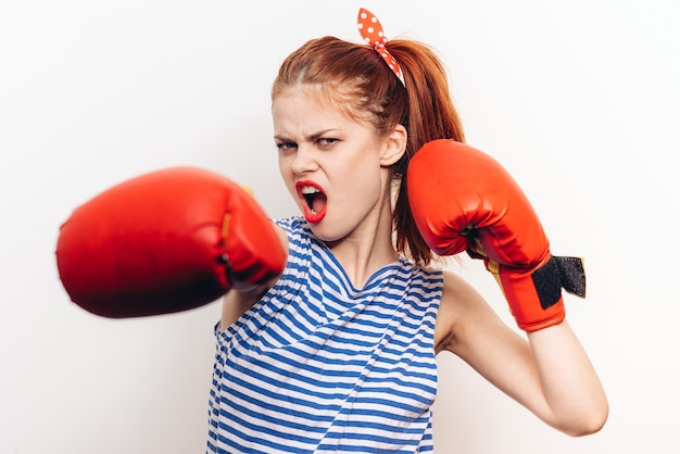 La donna in maglietta e guantoni da boxe rossi fa sport su sfondo chiaro. foto di alta qualità