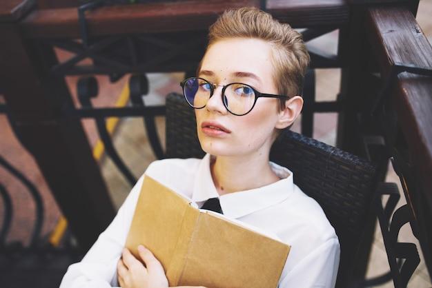 Donna al tavolo caffè design street libro studentessa con gli occhiali istruzione