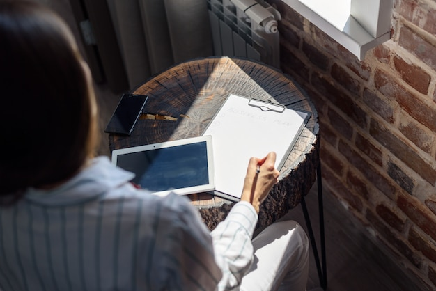 Donna al tavolo di fronte alla finestra con un tablet e un notebook, business plan, freelance, avvio