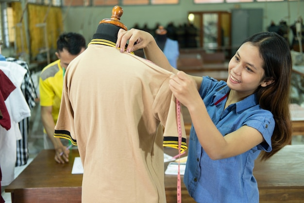Tessuto di misura sorridente su misura donna con con metro a nastro presso la sala di produzione di abbigliamento