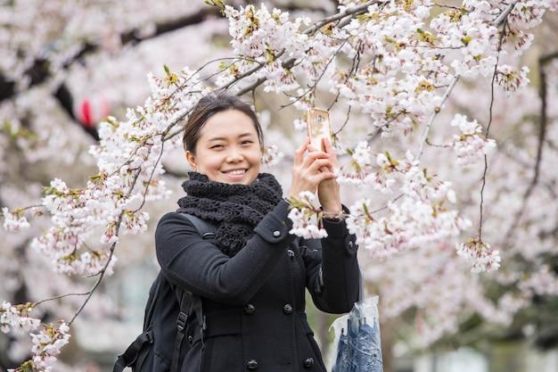 Una donna scatta foto di fiori di ciliegio con il cellulare in giardino hokkaido in giappone.