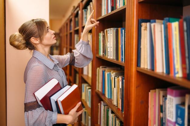 La donna prende il libro dallo scaffale nella biblioteca dell'università
