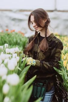 Una donna si prende cura dei fiori dei tulipani in giardino. primavera e estate. giardiniere donna felice con fiori.