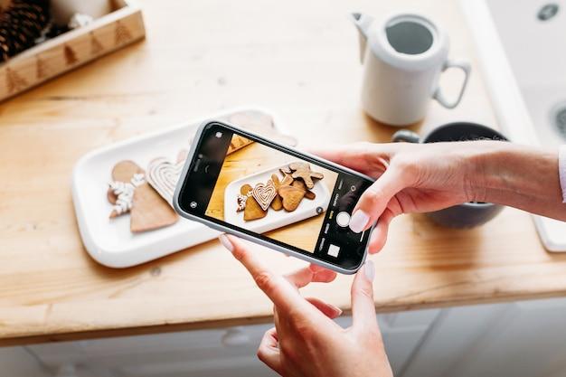 Una donna prende biscotti di natale, foto sul suo telefono, capodanno e social network sul suo telefono