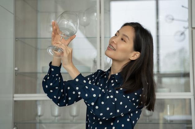 La donna prende un bicchiere dalla lavastoviglie mentre è in piedi in cucina