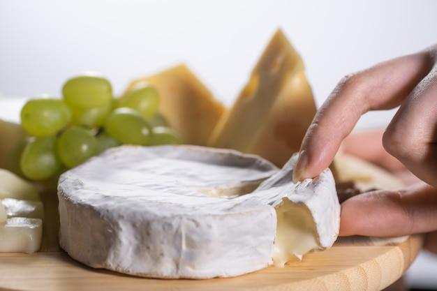 La donna prende un pezzo di camembert o brie