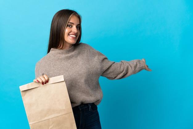 Donna che prende un sacchetto di cibo da asporto isolato su blu che estende le mani di lato per invitare a venire