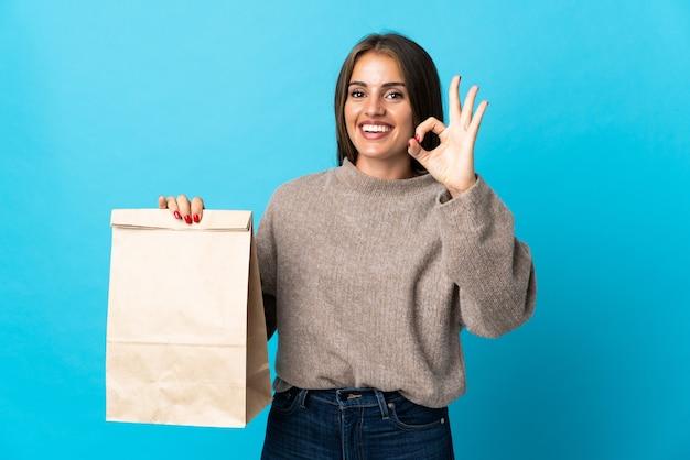Donna che cattura un sacchetto di cibo da asporto isolato sul blu che mostra segno giusto con le dita