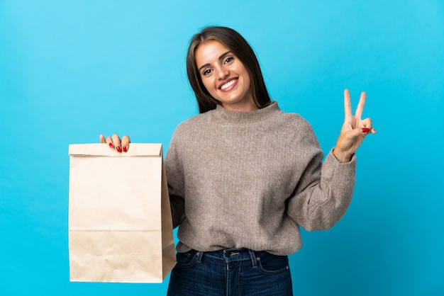 Donna che prende un sacchetto di cibo da asporto isolato su blu sorridendo e mostrando il segno di vittoria
