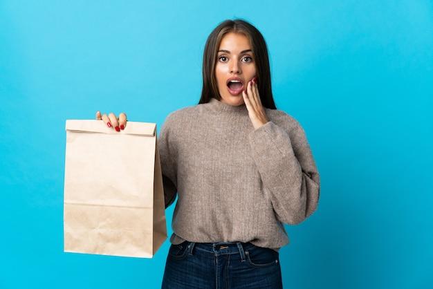 Donna che prende un sacchetto di cibo da asporto isolato sull'azzurro con espressione facciale sorpresa e scioccata