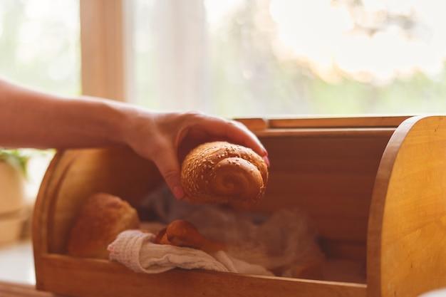 Donna che prende una pagnotta da una scatola di pane in cucina a casa