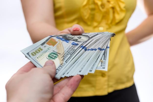 Donna che cattura il mucchio del dollaro dal primo piano maschio della mano