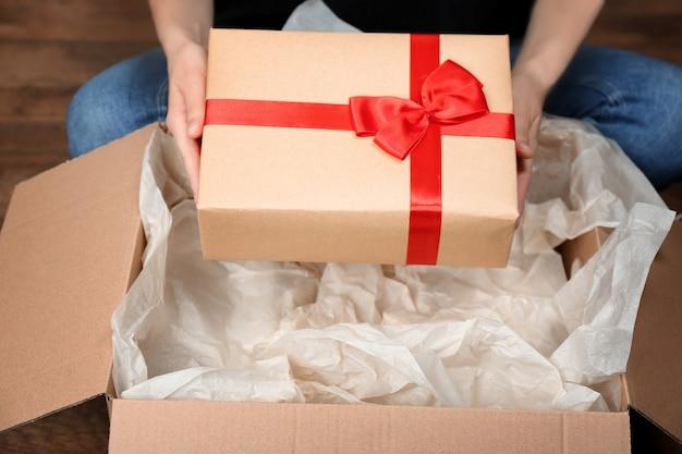 Donna che prende una scatola regalo dal pacco al chiuso