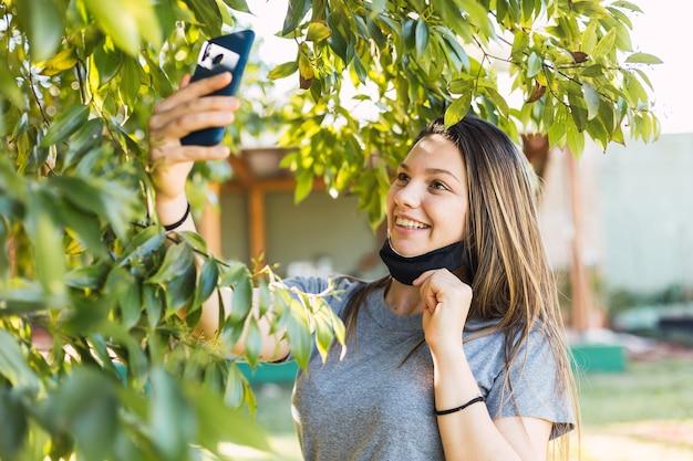 Donna che cattura selfie felice con maschera facciale aperta. nuovo stile di vita normale. concetto di viaggio e benessere.