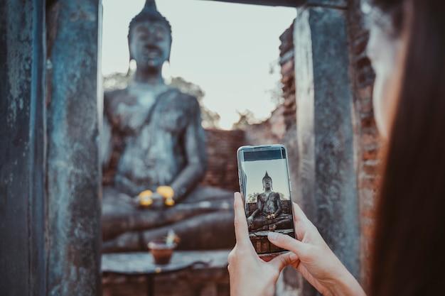 Donna che prende un'immagine orizzontale con il telefono dello schermo a buddha seduto in wat mahathat nel parco nazionale di sukhothai.