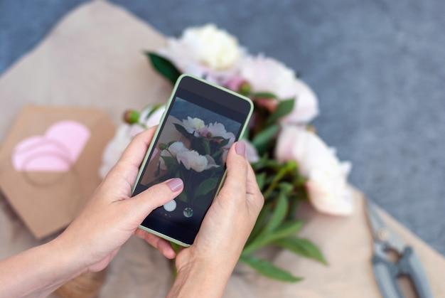 Donna che scatta foto mobile di fiori freschi, fiorista che fa bouquet e scatta foto con il telefono per i social network