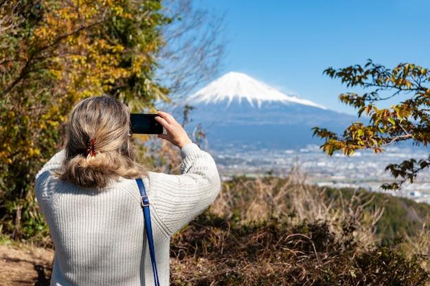 Donna che scatta una foto del monte fuji con una veduta aerea della città di fuji in giappone