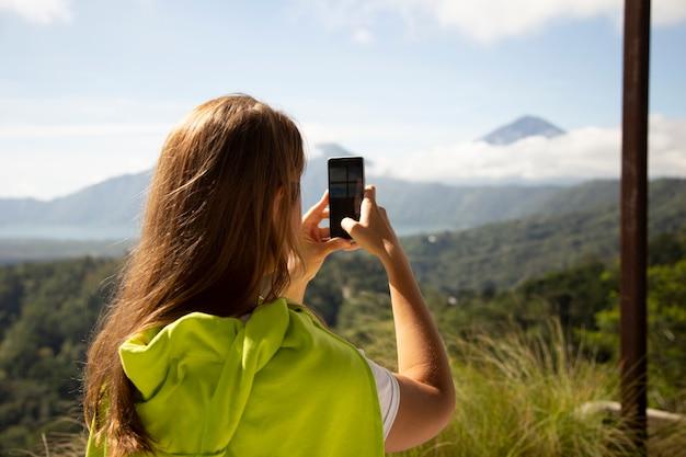 Donna che cattura foto di montagne con lo smartphone Foto Premium