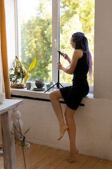 Donna che scatta foto di stoviglie in ceramica a casa Foto Premium