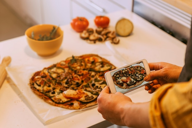 Donna che cattura foto a una pizza deliziosa. concetto fatto in casa.