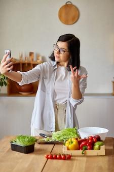 Donna che prende selfie o fa una lezione video sulla cucina, sul cellulare, smartphone per il suo blog sulla cucina a casa, concetto di blogger alimentare, stile di vita sano. trasmissione online