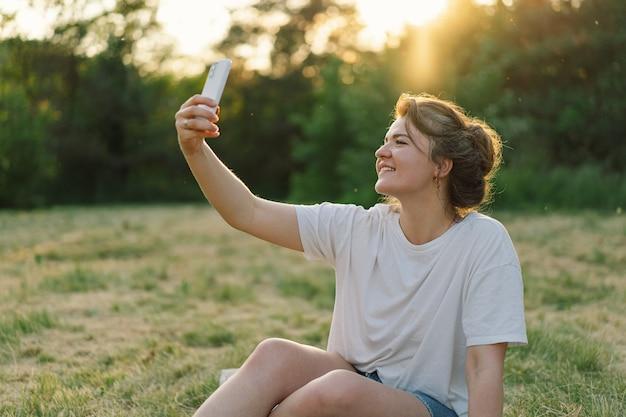 Donna che prende selfie sul concetto di mobilità dello stile di vita del telefono cellulare e sulla moderna tecnologia di co...