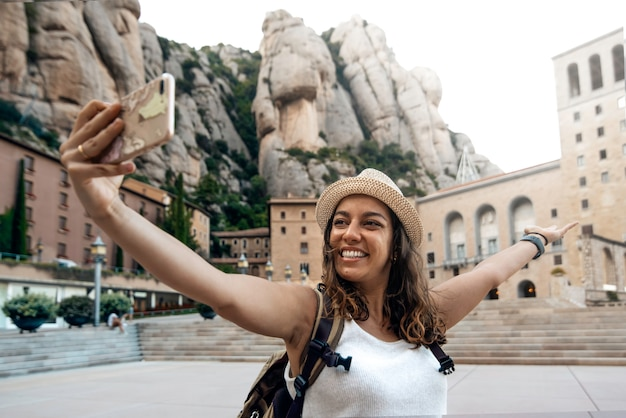 Donna che cattura una foto selfie nel monastero di montserrat, barcellona, spagna