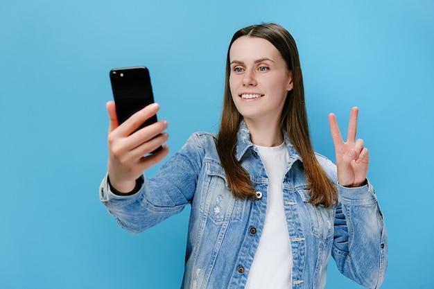 La donna che prende selfie con il telefono fa il gesto di pace