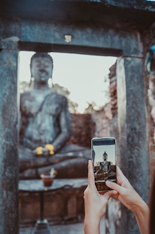 Donna che prende un'immagine verticale con il telefono dello schermo a buddha seduto in wat mahathat nel parco nazionale di sukhothai.