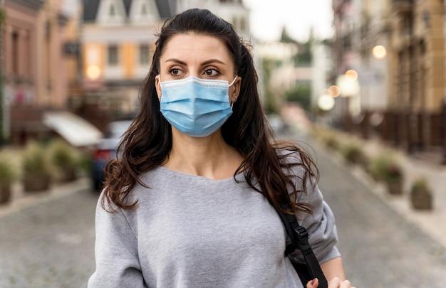 Donna che fa una passeggiata in città mentre indossa una mascherina medica
