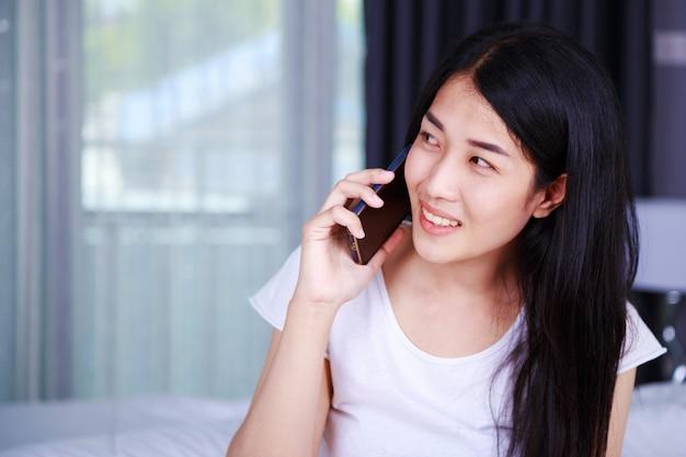 Donna che comunica sul cellulare sul letto nella camera da letto