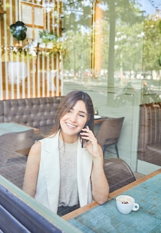 Donna che parla al cellulare in una caffetteria