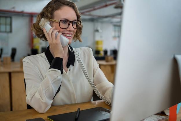 Donna che parla al telefono di rete fissa alla scrivania
