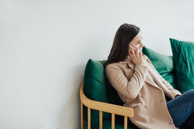 Donna che parla al telefono cellulare e che riposa nella caffetteria