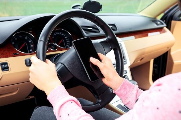 Donna che comunica sul cellulare mentre si guida l'auto