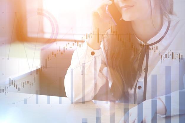 Donna che parla al telefono e grafici finanziari