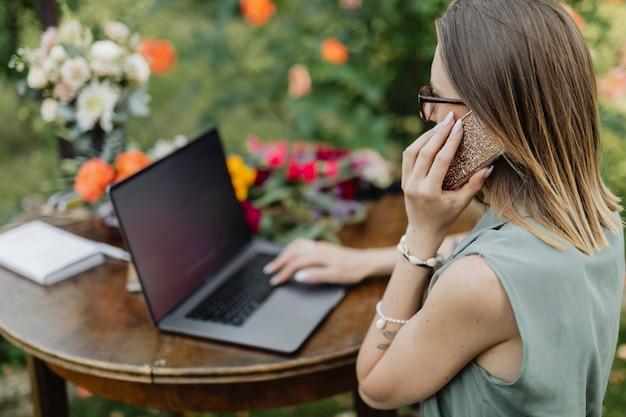 Donna che parla al telefono in giardino