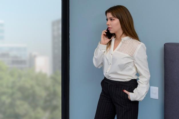 Donna che parla al telefono nella sua camera da letto