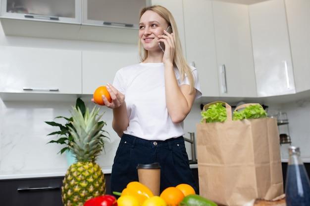 Donna che parla al telefono in cucina