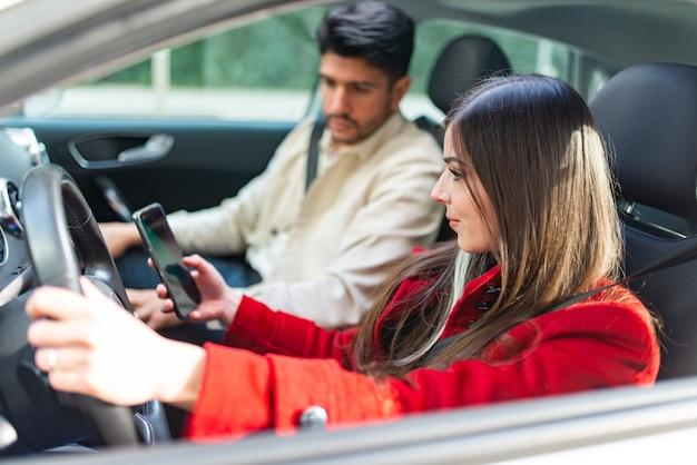 Donna che parla al telefono mentre guida la sua auto