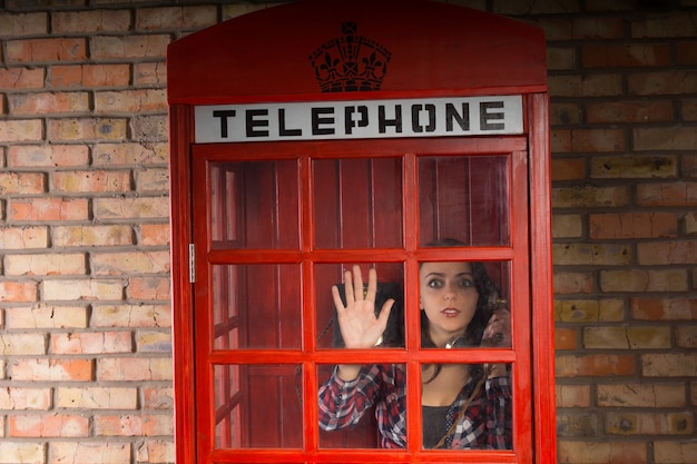 Donna che parla al telefono sbirciando da una cabina telefonica con orrore mentre nota qualcosa di terribile che accade fuori